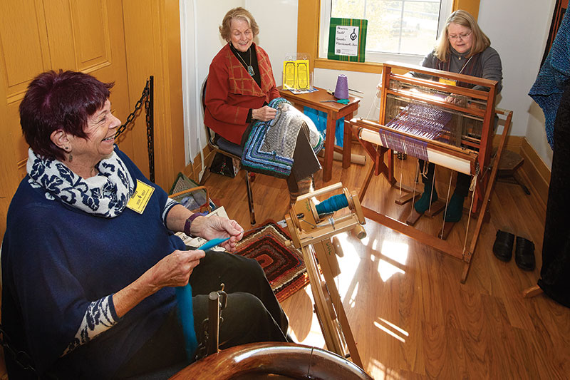 Weavers Guild of Greater Cincinnati board member Pat Maley spins during the annual Fiber Arts Sale. Photo by Al Parrish.