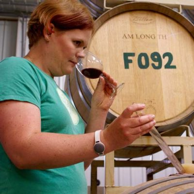 Lindsay testing a barrel of wine.