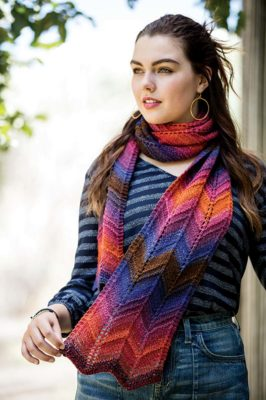 The Soldier Canyon Scarf, designed by Dani Berg, showcases a chevron pattern punctuated by purl ridges that transforms colorful yarn into eye-catching arrows.