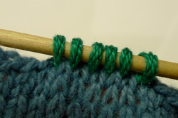 Pick up and knit is a two-step process when adding more stitches to a knitted piece.