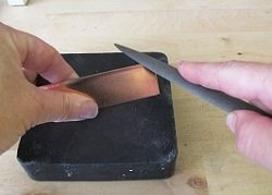 Use the half-round file first by placing the piece to be filed on a rubber block or other stable surface, as shown.