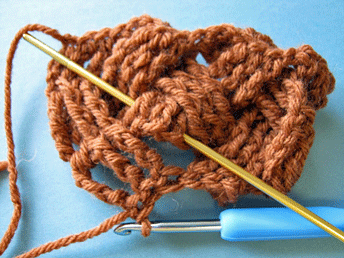 Edgeless Crochet Cables: Hiding stitches behind work on the third row (RS shown).