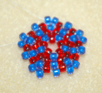 Learn how to do a circular flat peyote stitch in this expert beading blog, step 10 includes adding a pair of beads, then a single bead, and repeating around for a total of 15 beads added.