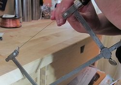 Steps to inserting a blade into the frame of a jeweler's saw.