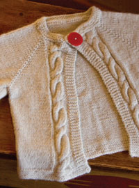 Create this cable knitted baby sweater in this free guide on baby knitting patterns.