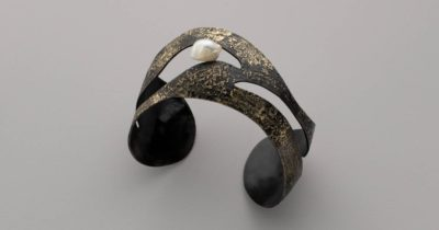 Worn against brilliant colors or neutrals, a blackened steel cuff splashed with gold and holding a shimmering pale pearl will always look terrific. Bette Barnett provides the bracelet how-to plus tips for making jewelry with steel, and talks about one of her favorite tools, all in Lapidary Journal Jewelry Artist January/February 2019. Photo: Jim Lawson