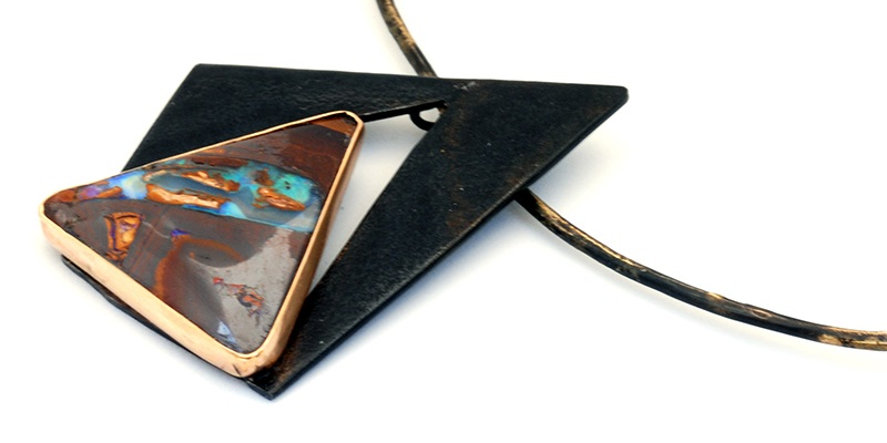 This steel and gold pendant by Bette Barnett makes an arresting frame for the blaze of color in this dark ironstone matrix of this Koroit opal. Photo courtesy Bette Barnett/Sparks Gallery.