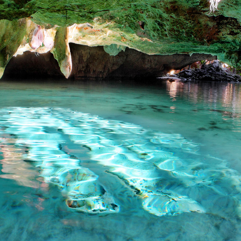 A cenote reveals a blue pool beneath bedrock.