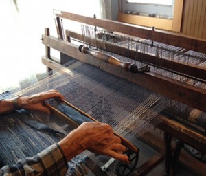 Charley weaving a denim rag rug on his loom.