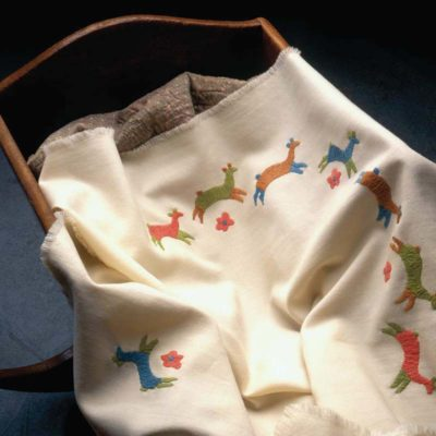 ColchaBaby_Resized / Caption: Colorful textured wool embroidery in the versatile colcha stitch decorates this off-white, lightweight wool baby blanket that is sure to become a family heirloom. Cradle courtesy of the Loveland Museum/Gallery, Loveland, Colorado.