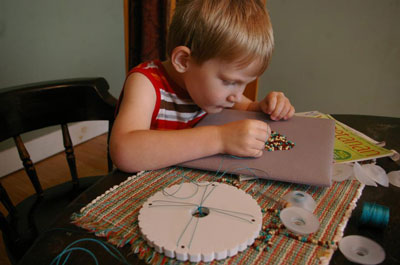 My son, then aged 4, stringing seed beads on my kumihimo cords for me