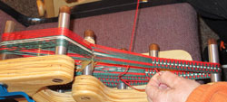Cookie Mesmer weaving on an inkle loom
