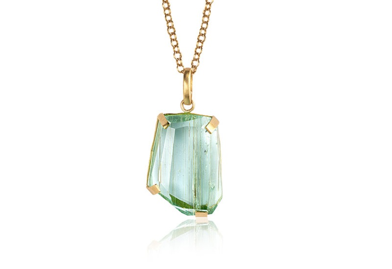This faceted blue-green aquamarine, set in a 18k yellow gold pendant by Eli Halili with a 22k yellow gold chain, contains eye-visible inclusions, but the unusual cut and the unique inclusions set it apart from any other aqua. Courtesy Eli Halili.