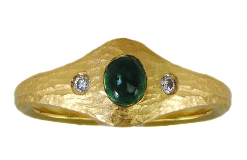"Emeralds are not always faceted. In fact, sometimes the depth of their color is best shown in cabochons, like the .39 ct emerald set in this 22k yellow gold ring. The lushness of the color all but shouts ""spring!"" Design by Michael Endlich, Photo by Sarah Francis, courtesy Pavé Fine Jewelry."