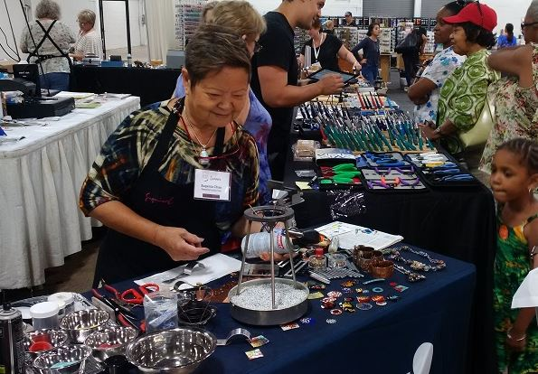 Eugenia Chan demonstrating jewelry making tools for riveting and enameling