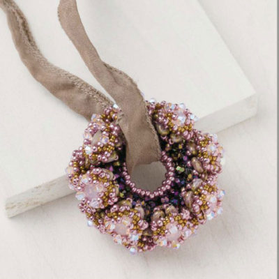Sabine Lippert's Radiant Wheel pendant, with a cubic-right-angle-weave ring adorned with bezeled chatons as seen in Favorite Bead Stitches Magazine 2017