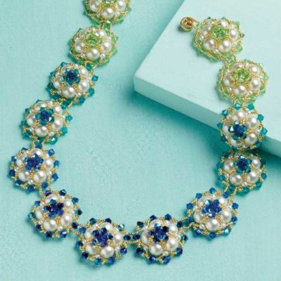 Wendy Lueder's stunning Bahamian Waters necklace, with its sapphire, turquoise, and light green bicones, intricately woven together with metallic gold seed beads