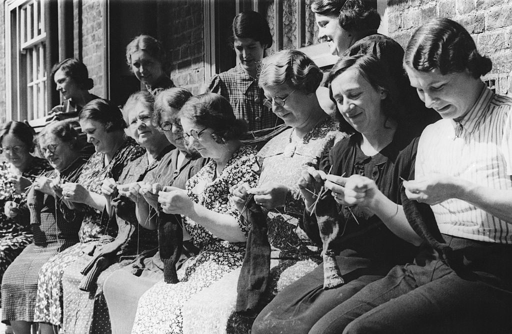 (Original Caption) From Salvage To Socks. The Children from the Duchy of Cornwall Estate in South London have formed a staunch little army of collectors and, headed by their Union Jack, they spend their playtime with their sacks on their backs collecting all the salvage they can This sorted out and sold and with the proceeds, the women of the Estate buy wool in order to knit socks for their men. Already over 50 pairs of socks have found their way to the man from the estate and both the children and the women tackle their jobs with great enthusiasm. Photo: With the wool bought from the proceeds of the children salvage efforts, the women of the Duchy of Cornwall estate knit socks for their men. 6th August 1940 (Photo by © Hulton-Deutsch Collection/CORBIS/Corbis via Getty Images)