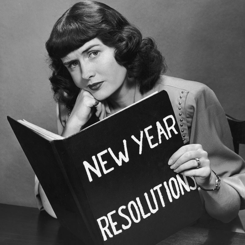 circa 1955: Studio portrait of a woman frowning with her chin resting on her hand, holding a large book titled 'New Year Resolutions'. (Photo by Harold M. Lambert/Lambert/Getty Images)
