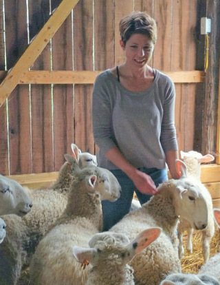 Kate Larson tending to her Border Leicester ewes. Photo by Maggie Smith