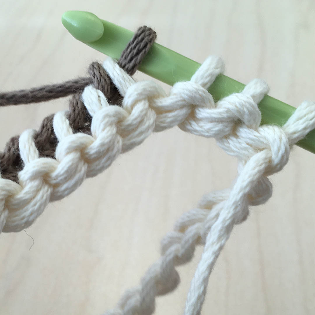 With second color, continue to yarn over and draw through 2 loops until 3-4 stitches remain on the hook. | Photo Credit: Sara Dudek