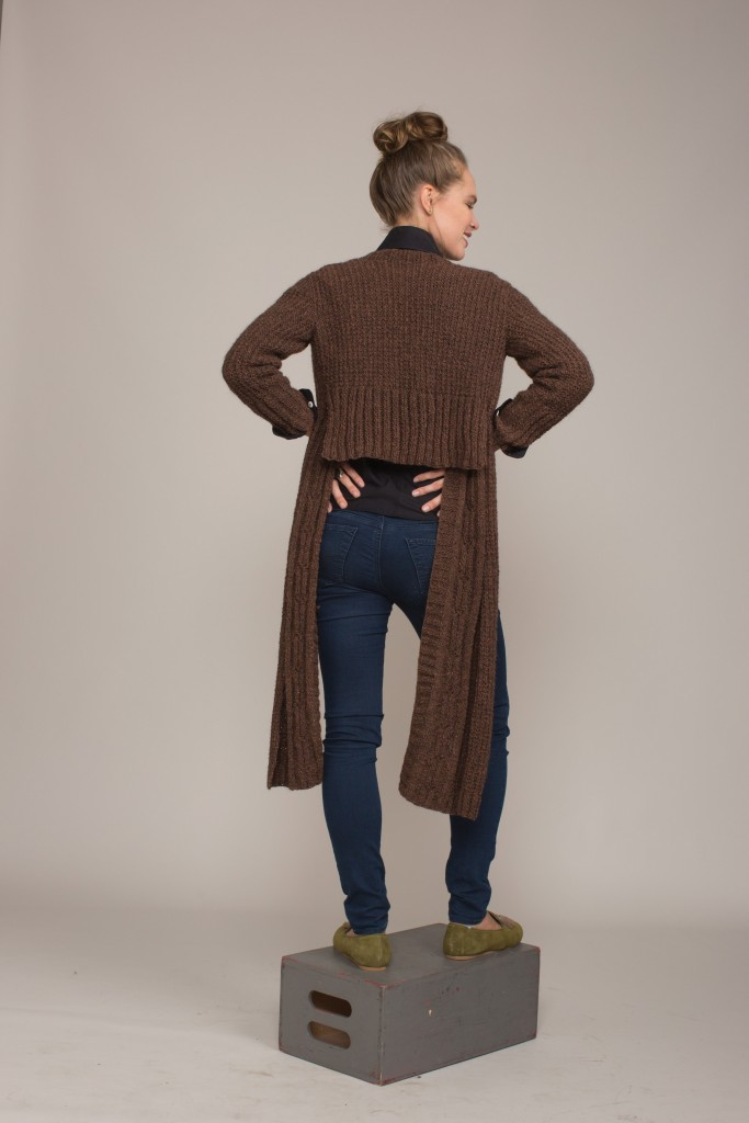 In a handsome heathered yarn with grandpa-sweater textures, this unusual knitted cardigan goes femme with a cropped back hem and extended fronts.