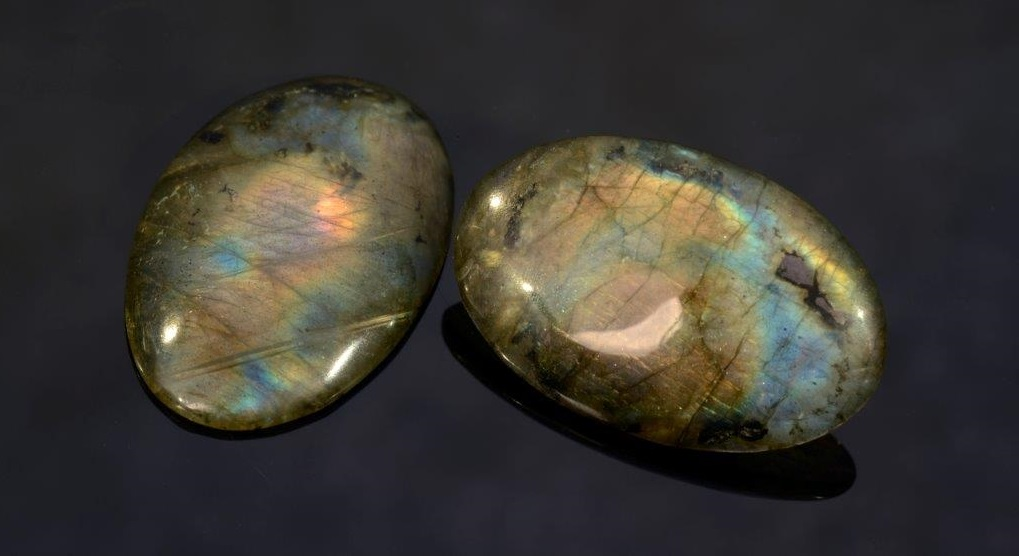 This pair of labradorites (32.64 carats total weight) exhibits the full range of spectral colors available to labradorite, from red though violet. In the stone on the left, you can see the lamellar structure that results in the changing colors of labradorite. Photo Mia Dixon, courtesy Pala International.