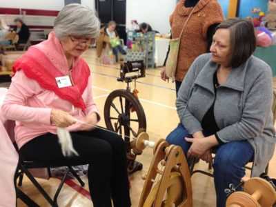 Betty Barry (left) discusses travel wheels with Mary, an intermediate spinner who wants to take her spinning on the road.