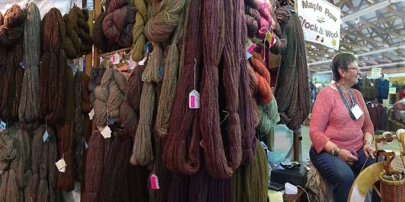 Deb Cline sits next to a veritable wall of her handspun in the Maple Row Stock and Wool booth.