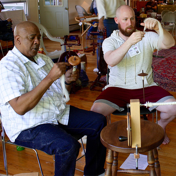 Men learn the basics of spinning fiber on a drop spindle. Pictured from left to right: Ron Green and Ben Walker. Photo by Joe Wilcox.