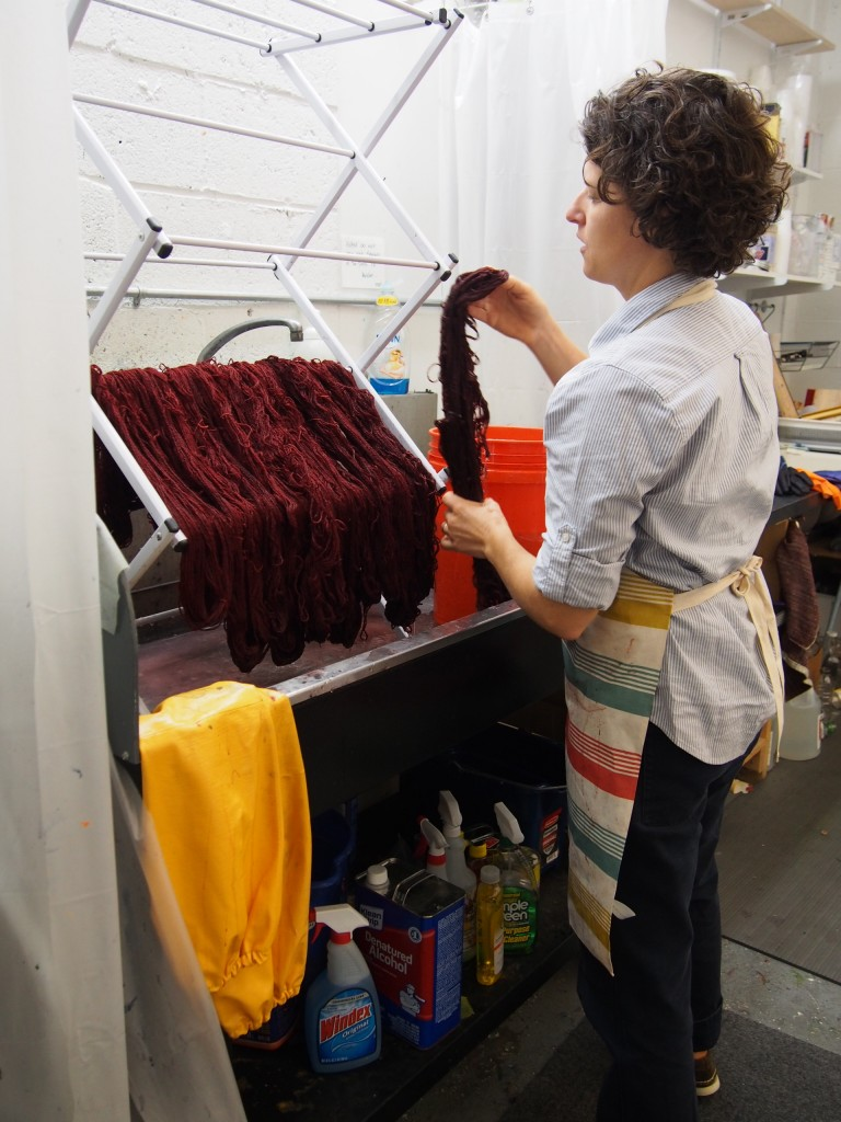 Sarah hangs dyed yarn to dry at her studio. Photo by Selma Moss-Ward.