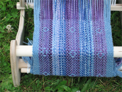 Blue scarf being woven on a rigid heddle loom