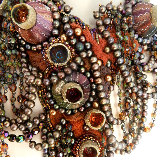 Barnacles is formed using Makustudios pods, wooden rings, seed beads, cheesecloth, freshwater pearls, and glass pearls.