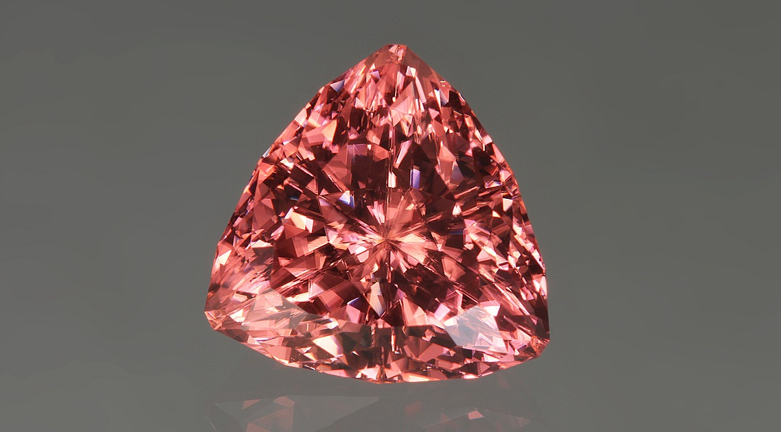 This lovely 7.20 carat salmon-pink colored, Super Trillion-cut zircon, was cut by John Dyer. Note the visible doubling of facets as you look through the stone. Photo by David Dyer, courtesy of John Dyer Gems.