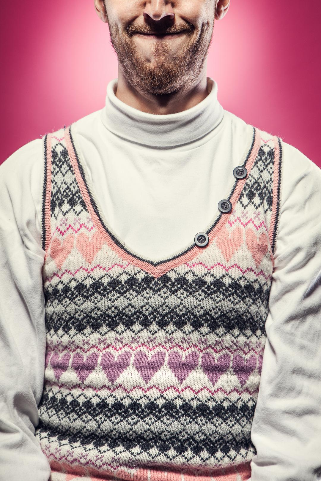 A man in a white turtleneck wears a wool sweater for Valentines day covered with knitted hearts. Vibrant pink background; studio shot.