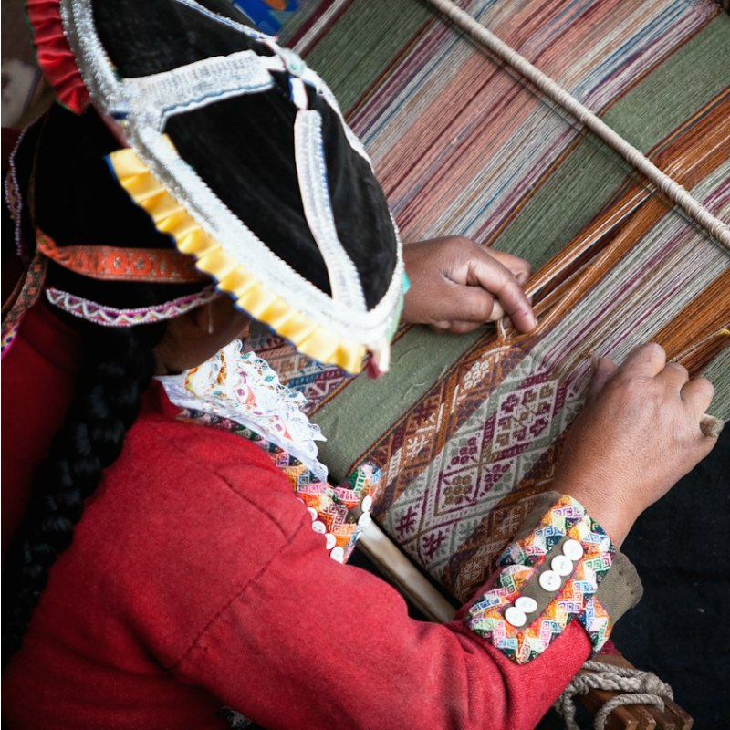 Unbroken Thread: A weaver works at a backstrap loom in Cusco, Peru. Photo by Julie Edgley.
