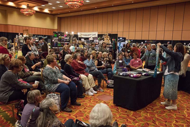 Yarn Fest attendees (ahem, fiber freaks) observe a demo in the marketplace.