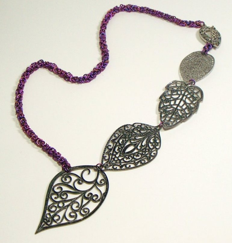 This asymmetric neckpiece shows an anodized chain and naturally colored focal.