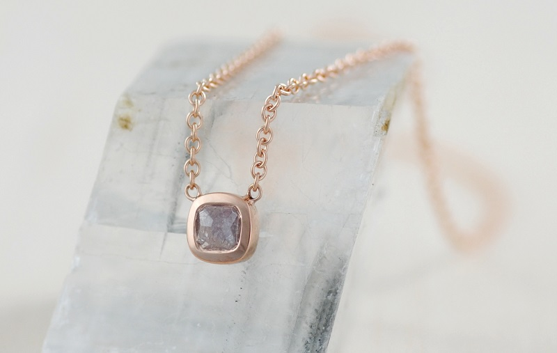 The imperfect perfection of wabi-sabi is seen in this 18k rose gold pendant by Michael Endlich. The grayish pink of the diamond is enhanced by the rose gold setting. The inclusions in the diamond, which make the stone almost opaque, make the stone and the pendant unique. Design by Michael Endlich, photo by Sarah Francis, courtesy Pavé Fine Jewelry.
