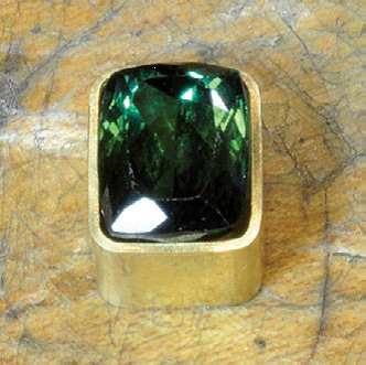 Making a bezel for a rectangular faceted stone with curved sides presents special challenges. Green tourmaline in partially built bezel by Bill Fretz; photo: Bill Fretz