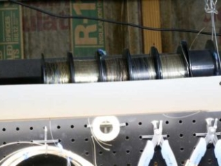 PVC pipe with wire spools held securely in place, hung from the ceiling.