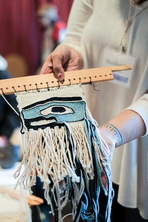 Weaver Shaadootlaa Tinaa'Yeil Gunaxoo'Kwaan displays a Ravenstail weaving woven with thigh spun warp. Photo: Kathy Cadigan.